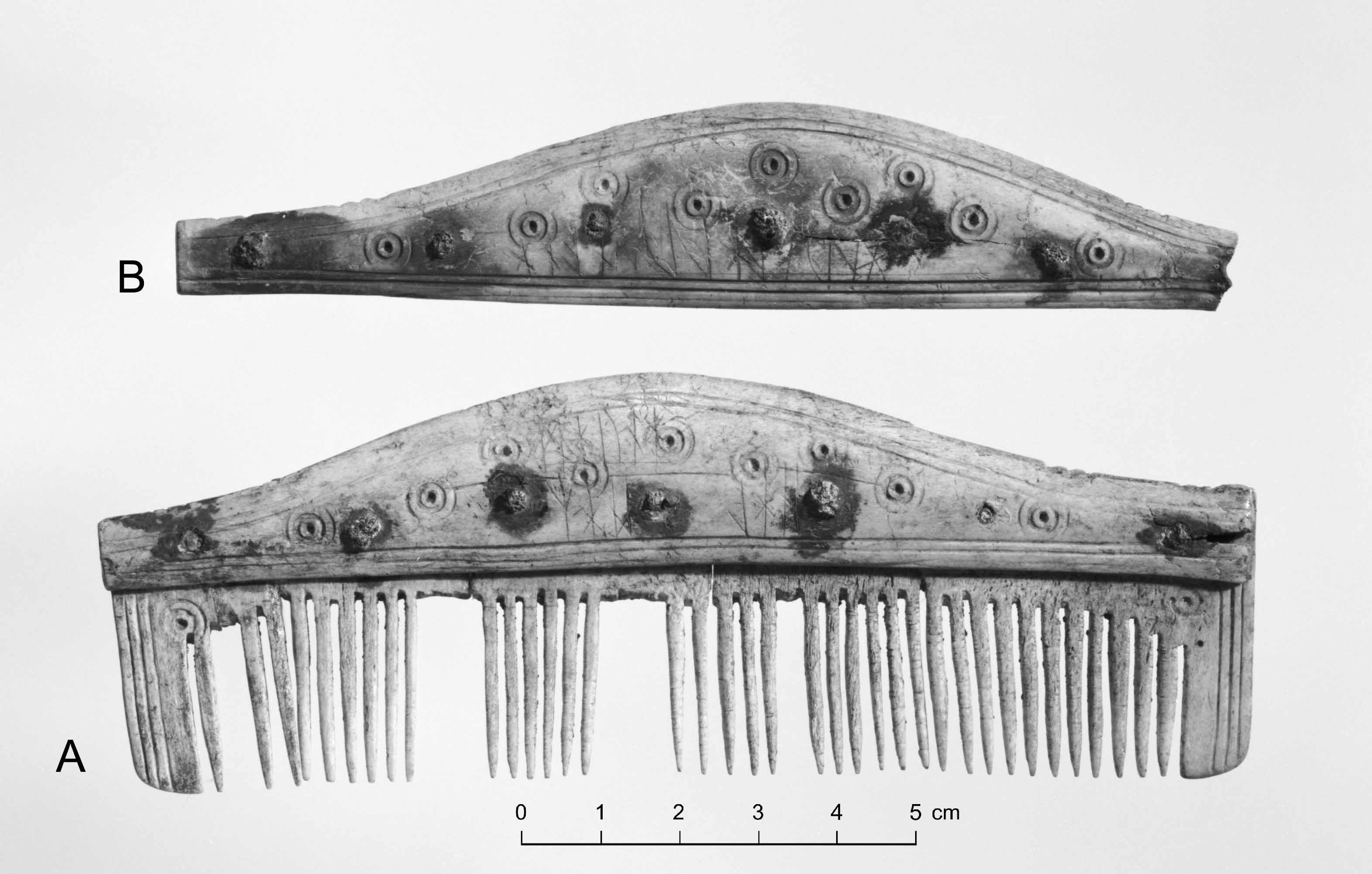 """einkammen med runeinnskrift. Legg merke til """"nittane"""" av jarn som vart nytta til å feste beinplatene saman."""