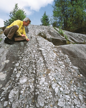 Geologist William Helland-Hansen examining a quartz conglomerate in the Ulven Syncline on one of the hills by the north west end of Lake Ulvenvatnet.