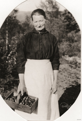 A picture from the 1930s; a woman with a typical strawberry basket made of wood.
