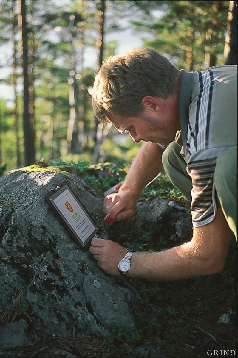 Naturforvalter Håvard Bjordal monterer verneskilt i Gullbergnotten, Jondal